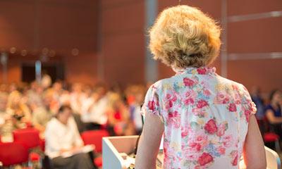 אשה מרצה באולם מול קהל
