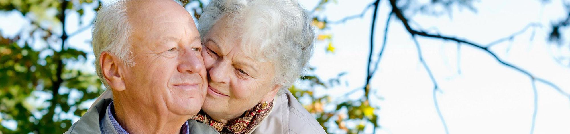 זוג קשישים אוהבים מצמידים ראשים על רקע עץ ושמיים