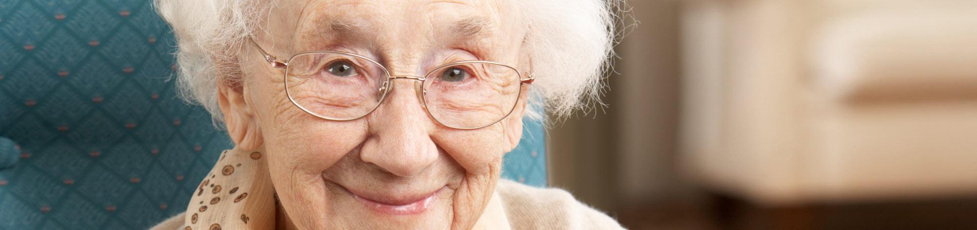 אישה מבוגרת עם משקפיים מחייכת