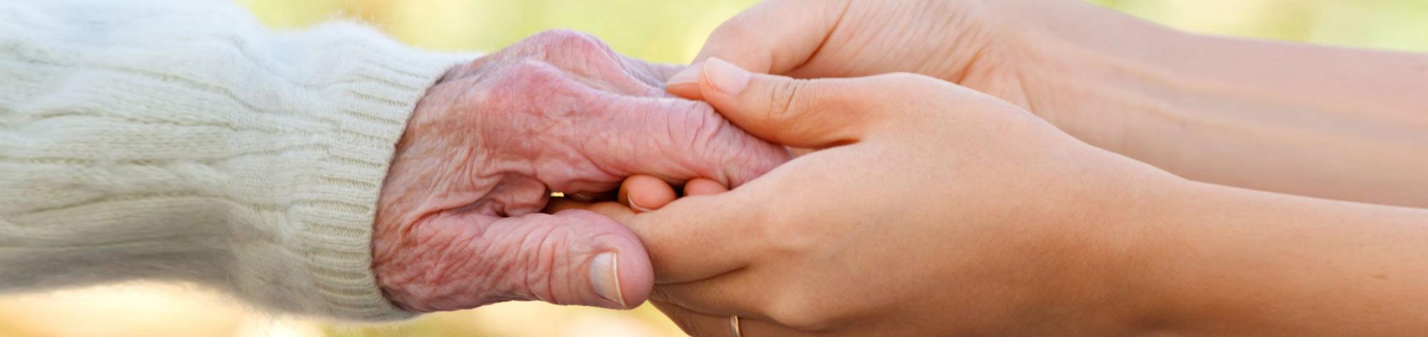 זוג ידיים של נערה אוחזות ביד של קשישה