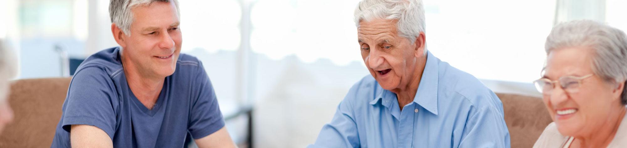 גבר בגיל העמידה יושב לצד הוריו המבוגרים